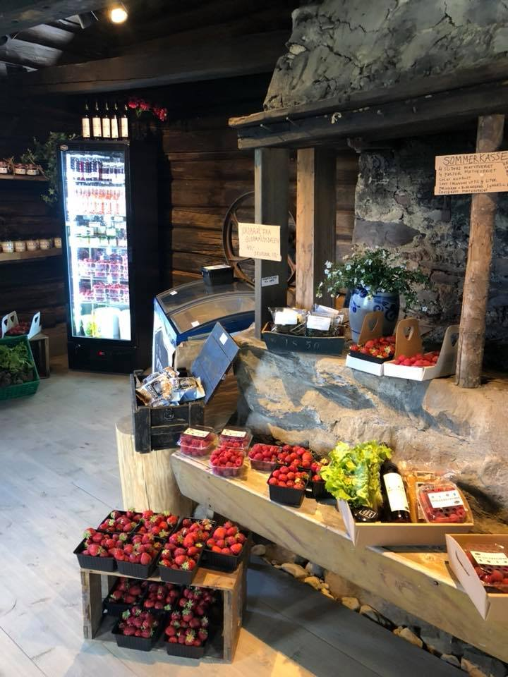 butikk med diverse matvarer og bær i et gammelt stabbur med tømmervegger