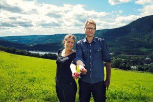 En dame og en mann står i en eng med utsikt over fjell og vann og byr fram bringebær