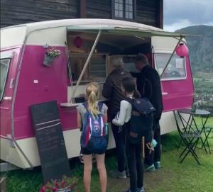 rosa med hvitt campingsvogn som med stor luke der det serveres mat og drikke fra